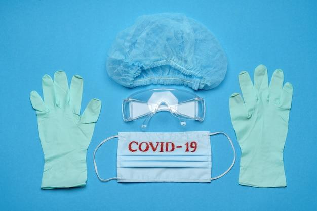 Máscara facial médica azul descartável com sinal covid-19, óculos de proteção, luva de látex de borracha e chapéu em fundo azul