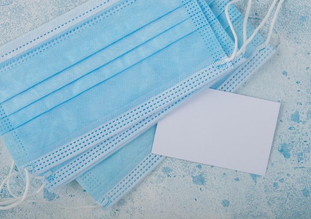 Máscara facial médica com cartão branco sobre azul. melhor proteção contra coronavírus, germes, bactérias e vírus. para uso hospitalar e diário. espaço para texto