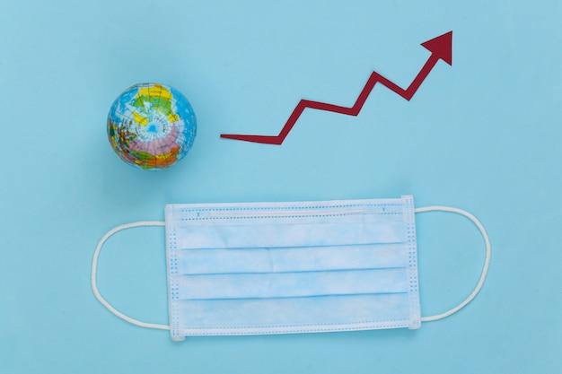 Máscara facial médica com globo, seta de crescimento tendendo para cima em um azul. pandemia mundial