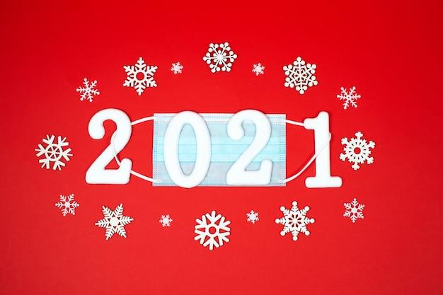 Máscara facial médica de natal e ano novo de 2021 e flocos de neve brancos sobre um fundo vermelho. ano novo novo normal. pandemic christmas.