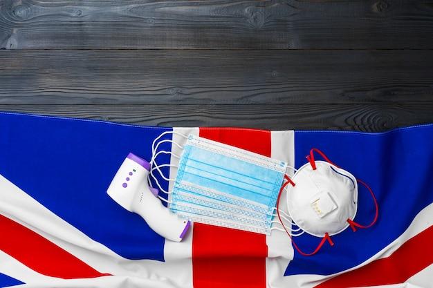 Máscara facial médica e termômetro sem contato na bandeira britânica