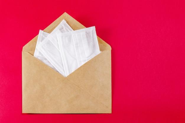 Máscara facial médica em um envelope cinza em vermelho