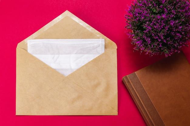 Máscara facial médica em um envelope vermelho com um bloco de notas marrom e uma flor lilás