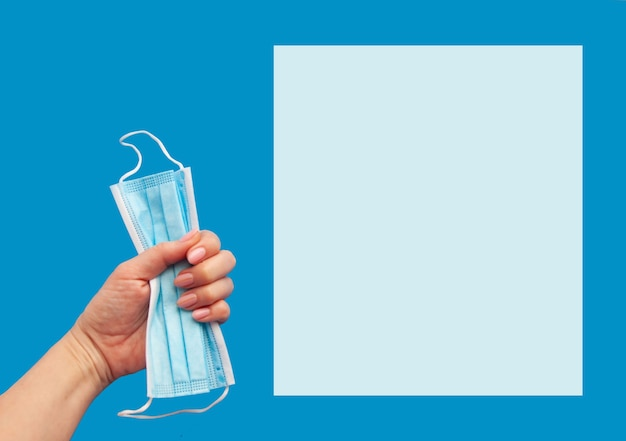 Máscara facial médica para proteção contra germes e poluição em um fundo azul. copie o espaço.