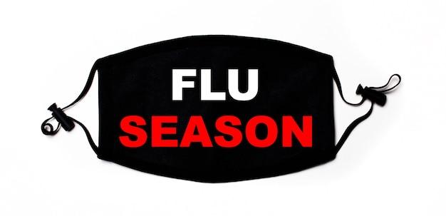 Máscara facial médica preta sobre uma superfície clara com a inscrição flu season. prevenção de doença. conceito médico