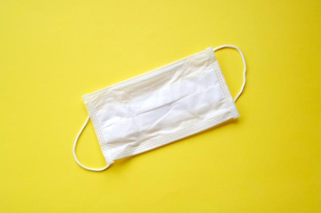 Máscara facial protetora médica branca anel de orelha higiênico ou cirúrgico em closeup amarelo. coronavírus covid-19, conceito de proteção e proteção ambiental contra vírus e bactérias.