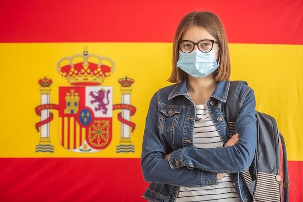 Máscara facial usando aluna carregando mochila com a bandeira espanhola no fundo.