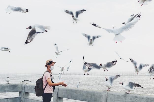Máscara facial vestindo asiática alimenta a comida de gaivota na praia ao fundo do mar.