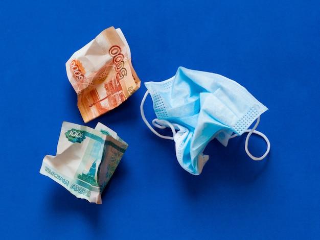 Máscara médica amassada contra coronovírus e dinheiro russo amassado sobre um fundo azul.