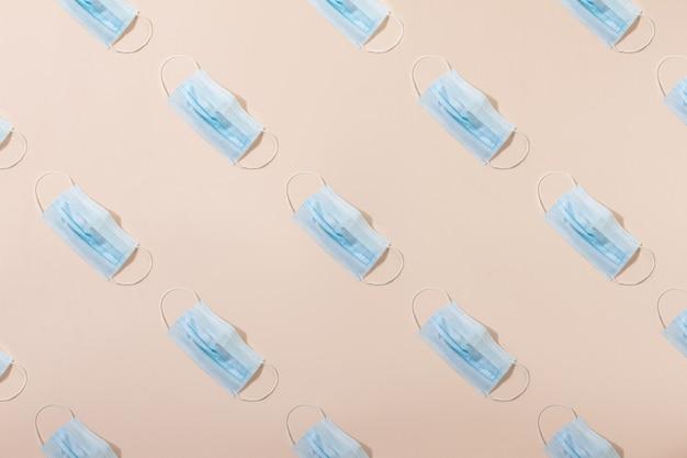 Máscara médica azul, sobre um fundo bege pastel com espaço de cópia como um padrão.