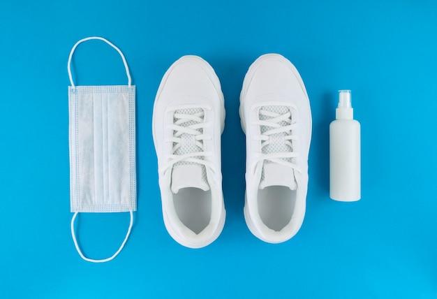 Máscara médica branca, tênis e desinfetante para as mãos sobre um fundo azul. camada plana monocromática. equipamento de quarentena.