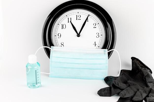 Máscara médica com relógio, higienização ge e luvas médicas pretas em fundo branco, conceito de tempo para vacina e covid