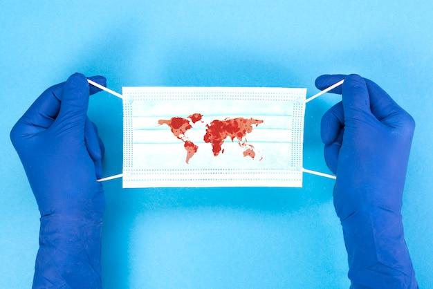 Máscara médica descartável com o contorno dos continentes do planeta nas mãos de um médico sobre um fundo azul, conceito de pandemia. covid-19, coronavírus. epidemia global da doença.
