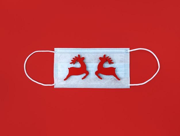 Máscara médica e brinquedos de madeira para cervos em uma superfície vermelha