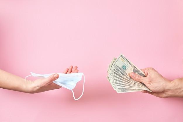 Máscara médica e dólares na mão como um conceito de aumento de preços para proteção contra vírus.