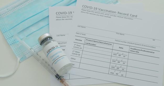 Máscara médica e vacina covid-19 no cartão de registro de vacinação aprovado pelo cdc com frascos de vacina de vírus corona.