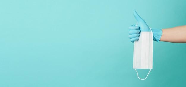 Máscara médica em fundo azul e verde ou azul tiffany. mão use luva cirúrgica e segurando a máscara facial. e fazendo o sinal de mão