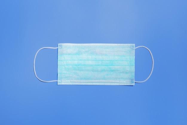 Máscara médica em uma vista superior do plano de fundo azul