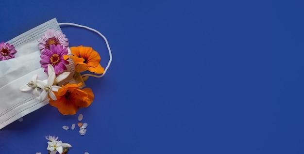 Máscara médica flores no topo com flores de cores diferentes na vista superior de fundo azul com espaço para texto. conceito de quarentena deoronavírus