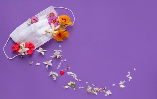 Máscara médica flores no topo com flores de cores diferentes no fundo rosa lilás vista superior com espaço no meio. vitória do conceito de quarentena deoronavírus