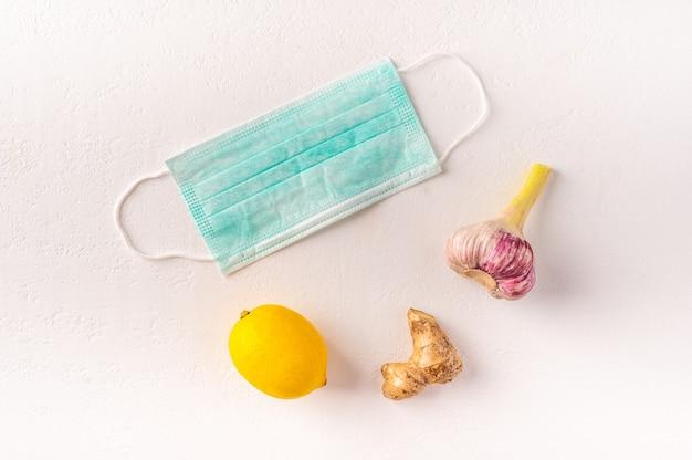 Máscara médica, limão, gengibre e alho em um fundo claro