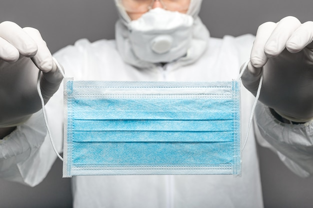 Máscara médica, máscara protetora médica nas mãos de médicos contra covid-19