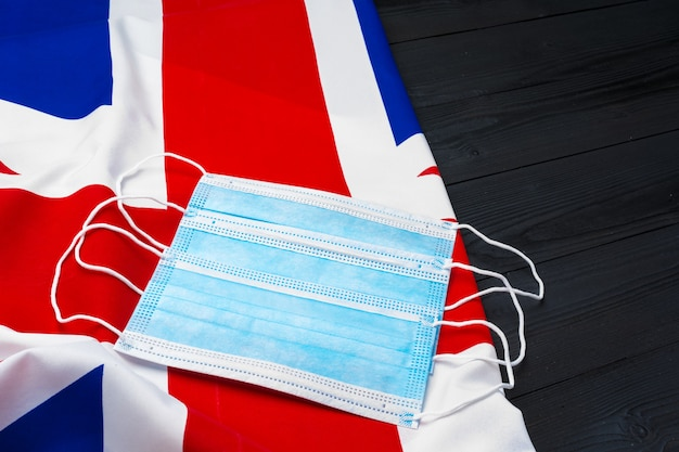 Máscara médica na bandeira do reino unido, conceito de coronavírus