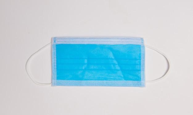 Máscara médica na vista de cima plana de superfície branca com espaço de cópia. proteção contra vírus, coronavírus, gripes, resfriados, doenças. ferramenta médica tradicional, conceito de saúde.