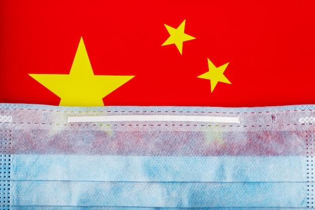 Máscara médica no fundo da bandeira chinesa. máscaras descartáveis para vírus, coronavírus