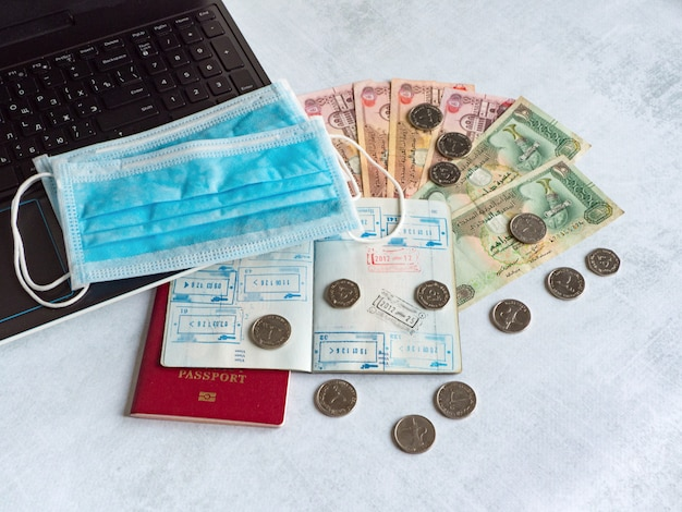 Máscara médica, passaporte com vistos e dirhams árabes. pandemia e a crise econômica do conceito