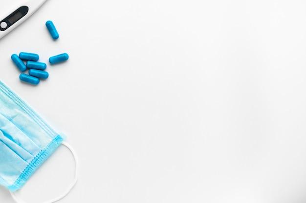 Máscara médica, pílulas e termômetro eletrônico digital