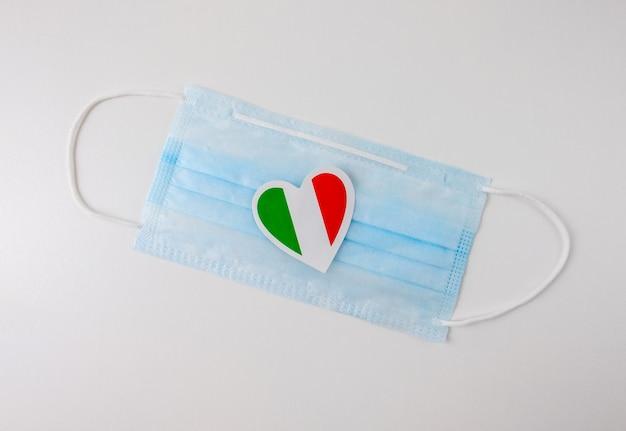 Máscara médica protetora azul com uma miniatura da bandeira da itália no formato de um coração