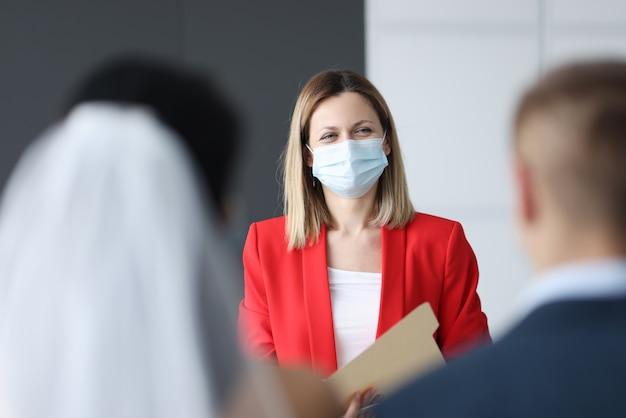 Máscara médica protetora de mulher no rosto, registrando o casamento. casamento durante o conceito de pandemia covid-19