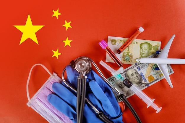 Máscara médica, tubos de análise de sangue, luvas de látex, avião de brinquedo, seringa e notas de dólar americano na bandeira chinesa