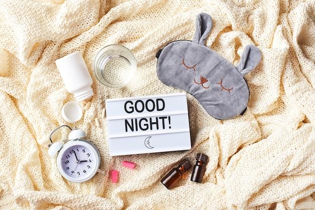 Máscara para dormir, despertador, tampões de ouvido, óleos essenciais e comprimidos. conceito criativo de sono de noite saudável. camada plana, vista superior. boa noite higiene do sono, insônia