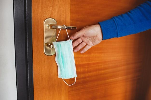 Máscara para evitar a infecção do coronavirus covid 19, pendurado na maçaneta da porta. conceito de prevenção antes de sair de casa.