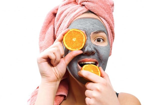 Máscara para mulher de pele, garota feliz e engraçada faz máscara para a pele do rosto, garota fecha os olhos com laranja, foto isolada, papel emocional de gênero