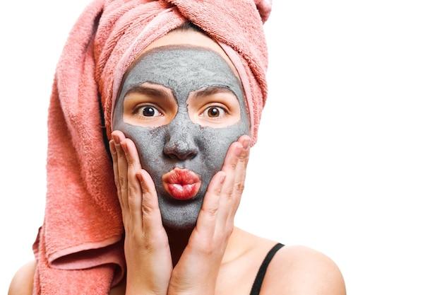 Máscara para mulher pele, garota divertida e feliz com máscara facial em um fundo branco, foto isolada, garota sopra os lábios
