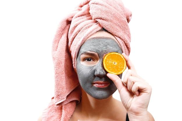 Máscara para pele de mulher, garota alegre e divertida faz uma máscara para pele de rosto,