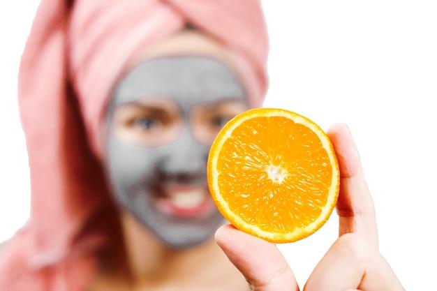 Máscara para pele de mulher, menina segurando uma fatia de laranja, laranja em primeiro plano, foto isolada