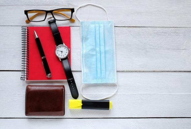 Máscara para sala de cirurgia, relógio de pulso, óculos, bloco de notas e caneta