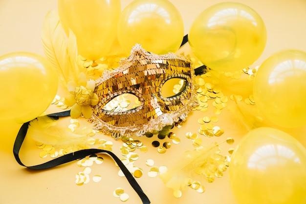 Máscara perto de balões e confetes