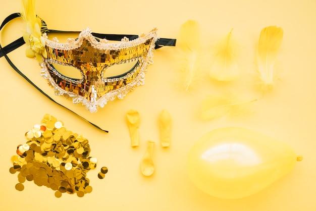 Máscara perto de brilhos, balões e penas