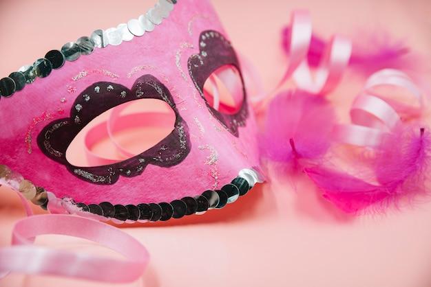 Máscara perto de espinhos de ornamento e fita