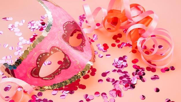 Máscara perto de fitas e conjunto de brilhos rosas