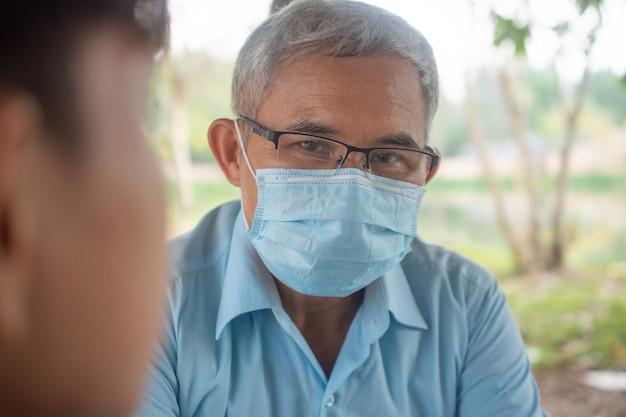 Máscara protetora asiática do doutor que verifica a freqüência cardíaca à mão