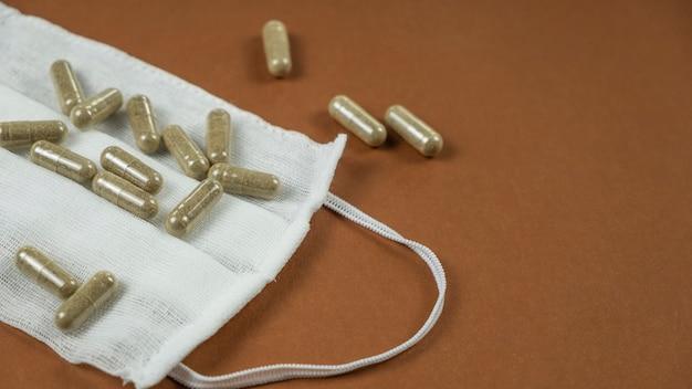 Máscara protetora de medicina e pílulas sobre fundo marrom, espaço de texto