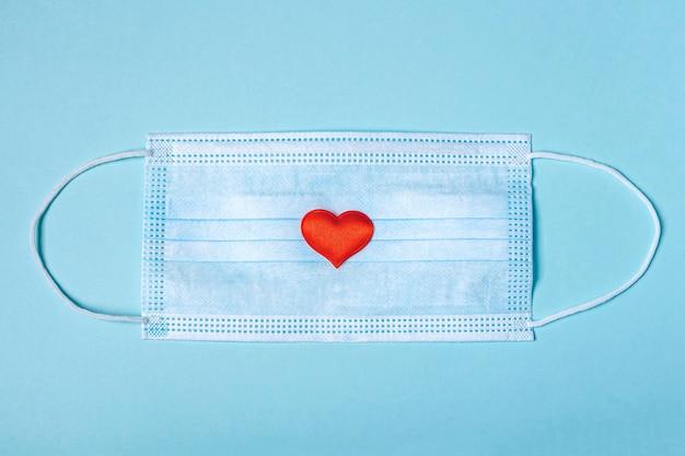 Máscara protetora de rosto médica e corações vermelhos e brancos sobre fundo azul. novo normal e coronavírus, conceito covid-19. postura plana,