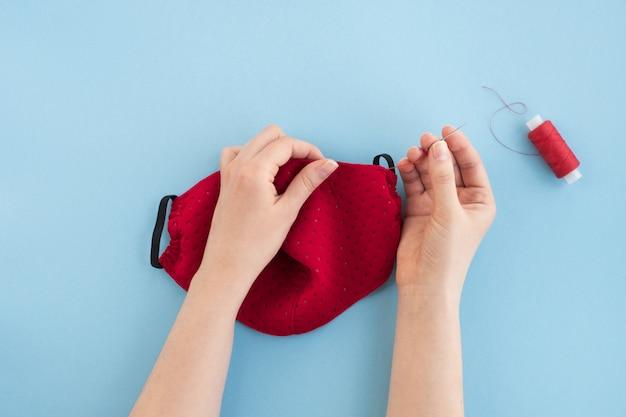 Máscara protetora de rosto médica no processo de costura