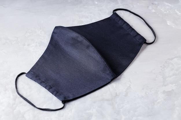 Máscara protetora facial em fundo cinza final. máscara antivírus. máscara negra caseira